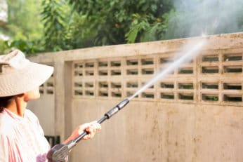 a woman using a water jet on the wall