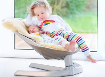 a baby and a toddler resting on a bouncer