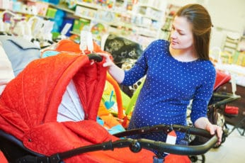 pregnant woman looking at a red pushchair