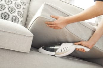 cleaning the sofa with a handheld hoover