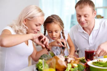 a mother cutting meat in a family dinner