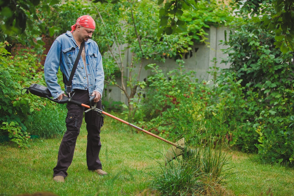 man using a cordless strimmer