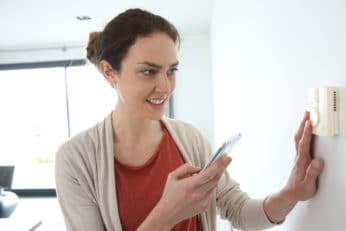 woman checking the wireless thermostat