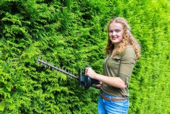 woman using a lightweight hedge trimmer