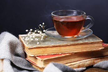 a cup of hot tea on top of some books
