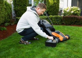 man putting a battery in his lawn mower