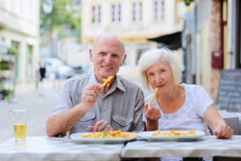 old couple eating fried food