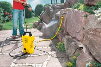 man using a pressure washer on stones