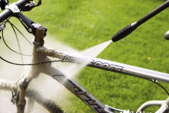 person cleaning a bike using a pressure washer