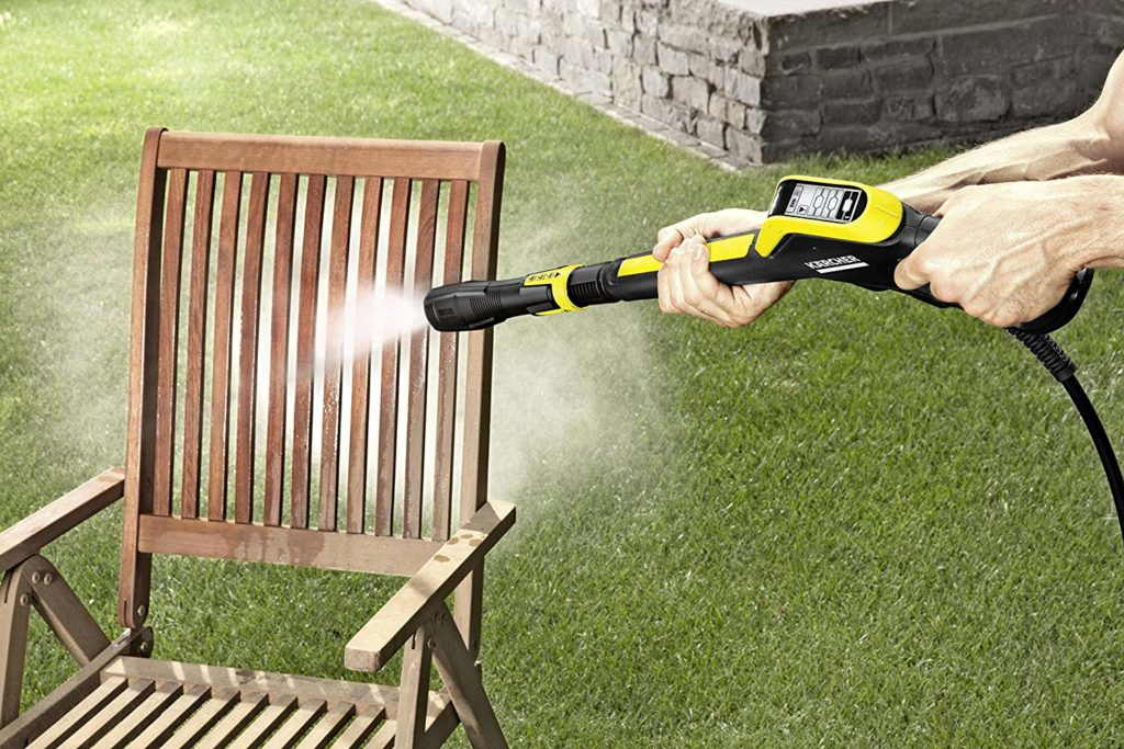 person using a pressure washer to clean a chair