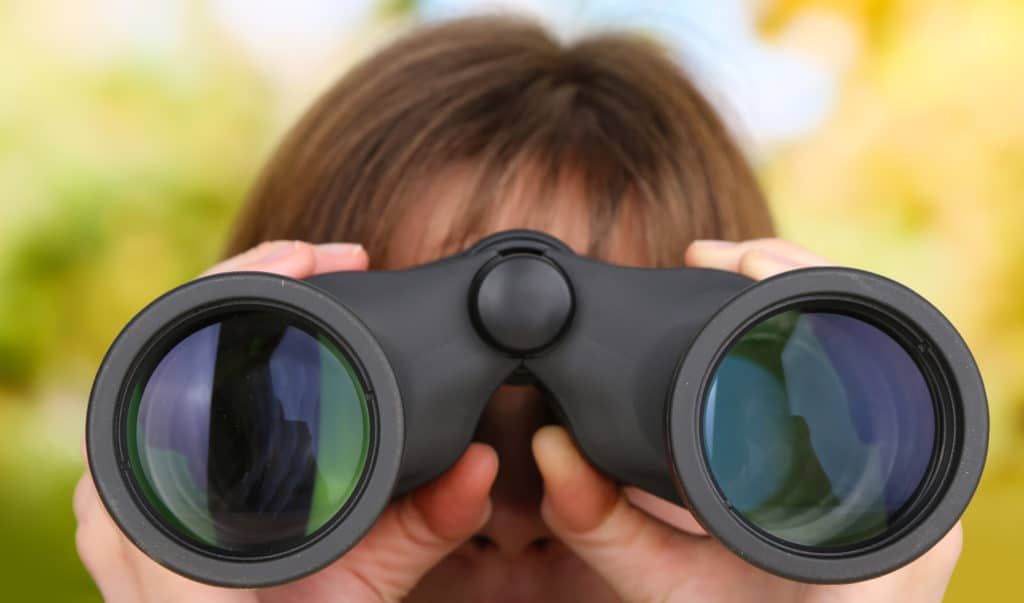 a person looking through a pair of binoculars