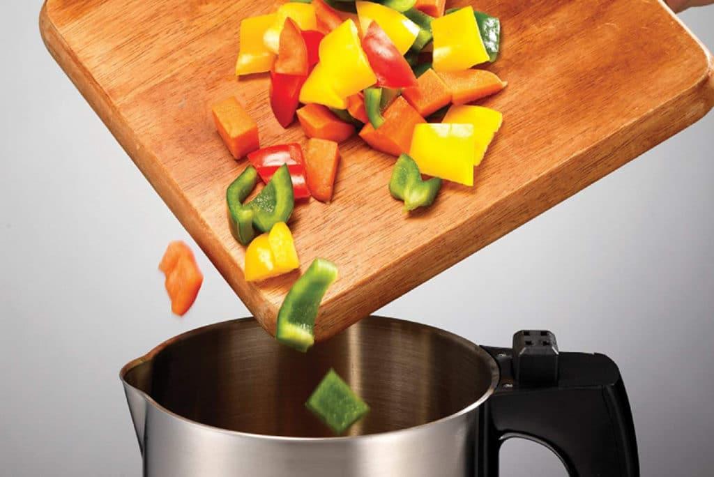 adding vegetables in a soup maker