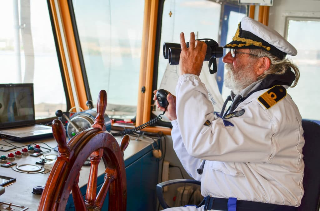 an old captain looking through a pair of binoculars