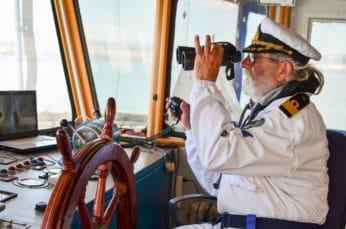 an old captain looking through a pair of binoculars
