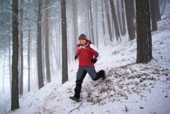 man running through a snowy mountain