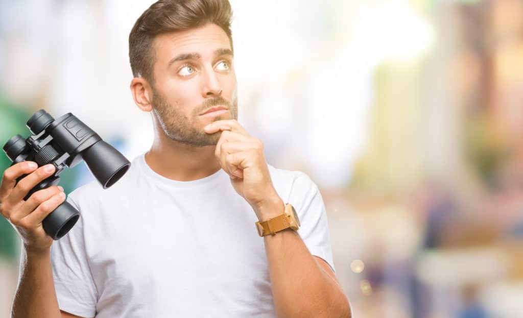 man thinking deeply while holding a pair of binoculars