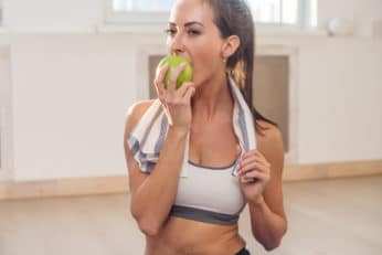 woman eating an apple after her workout