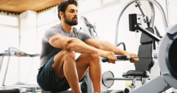 young man using a rowing machine in the gym
