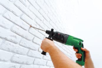 man drilling a concrete wall