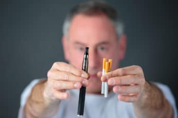 man with tobacco cigarettes and an electronic vaporizer