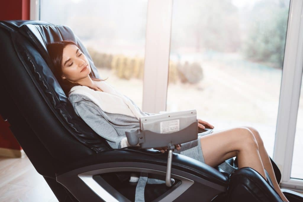 young woman relaxing on a massage recliner