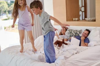 kids jumping on the bed of their parents