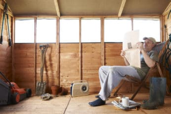 man reading the paper in his garden shed