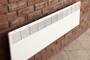 a convector mounted on a brick wall