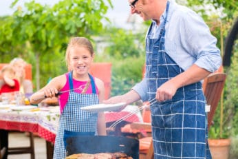 a girl helping her dad with the griller