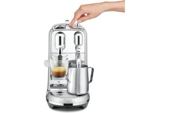 a hand touching a coffee device