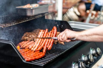 a person grilling steaks and sausages