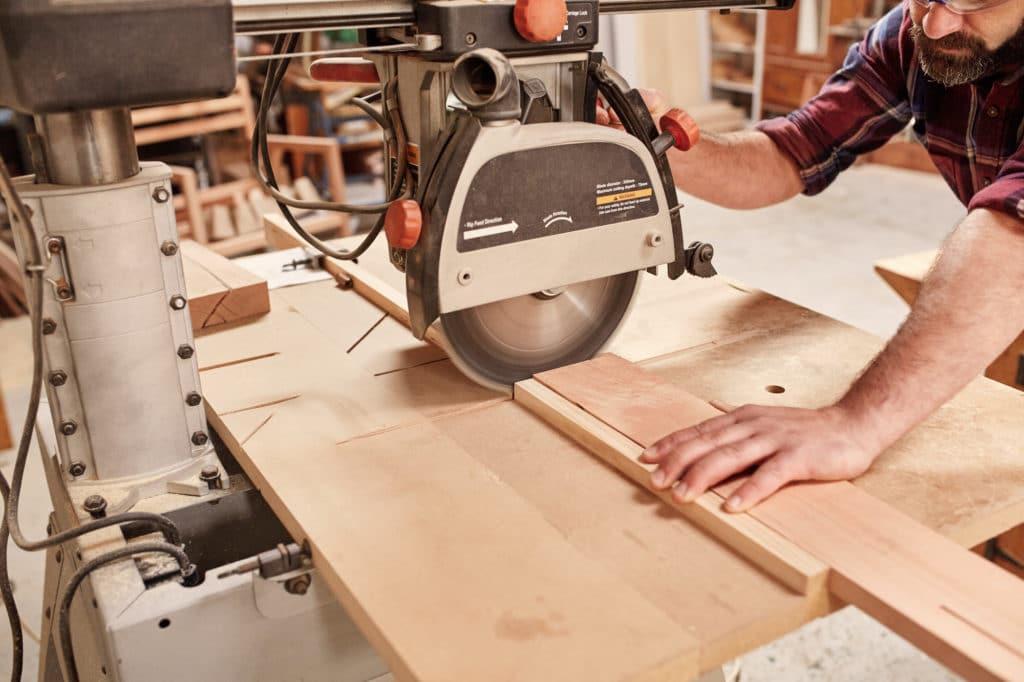 carpenter cutting a piece of wood