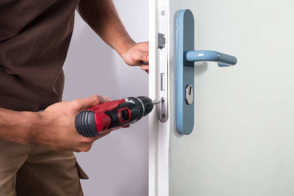 carpenter installing a door lock