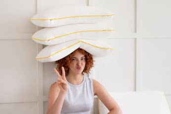 woman with pillows on her head