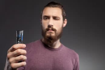young man scrutinising a beard trimmer