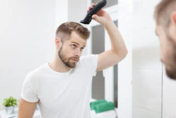 a man using hair clippers on himself