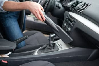 a man vacuuming his car's interior