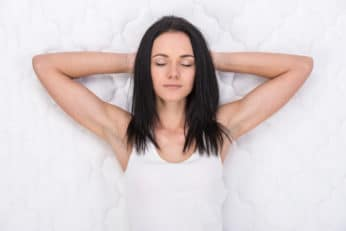 a lady comfortably lying on a mattress