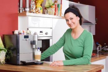 a lady waiting beside a coffee machine