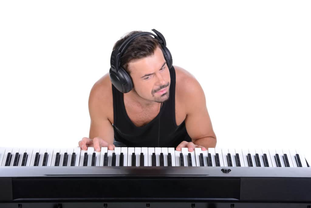 a man playing the piano with a headphone