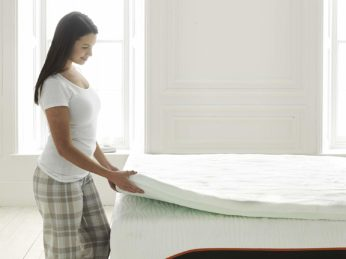 a woman lifting the edge of a mattress pad
