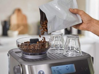 pouring coffee beans into a coffee grinder