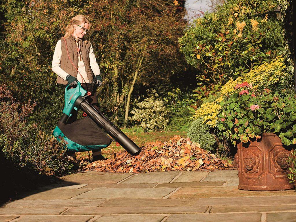 a lady using a leaf blower machine