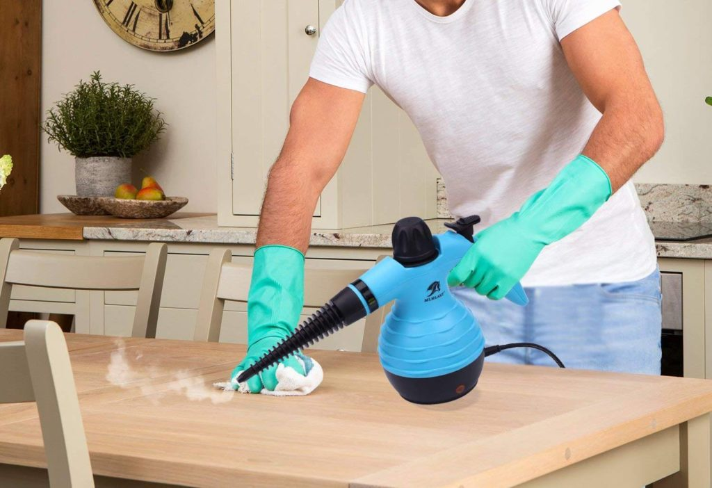 a man steam cleaning a wooden table