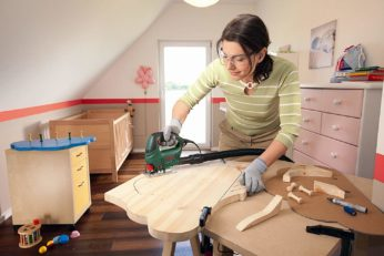a mother carving wood with a jigsaw
