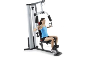 a woman working out with a multi gym