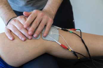 electronic therapy on knee used to treat pain. selective focus