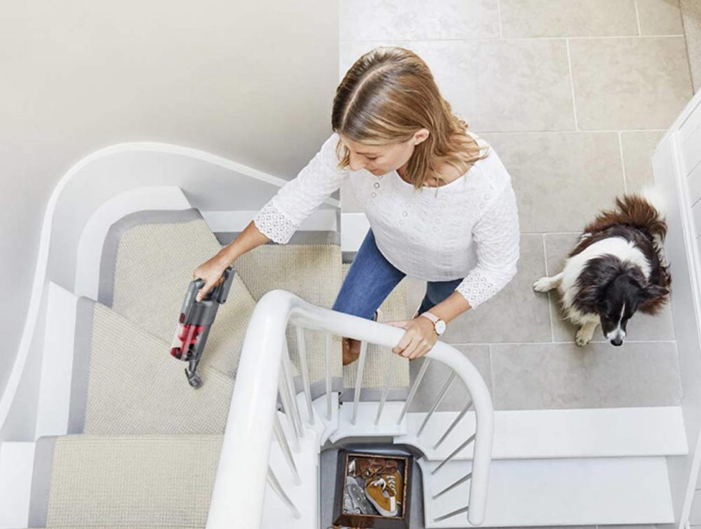 a lady cleaning the stairs with a dog beside her