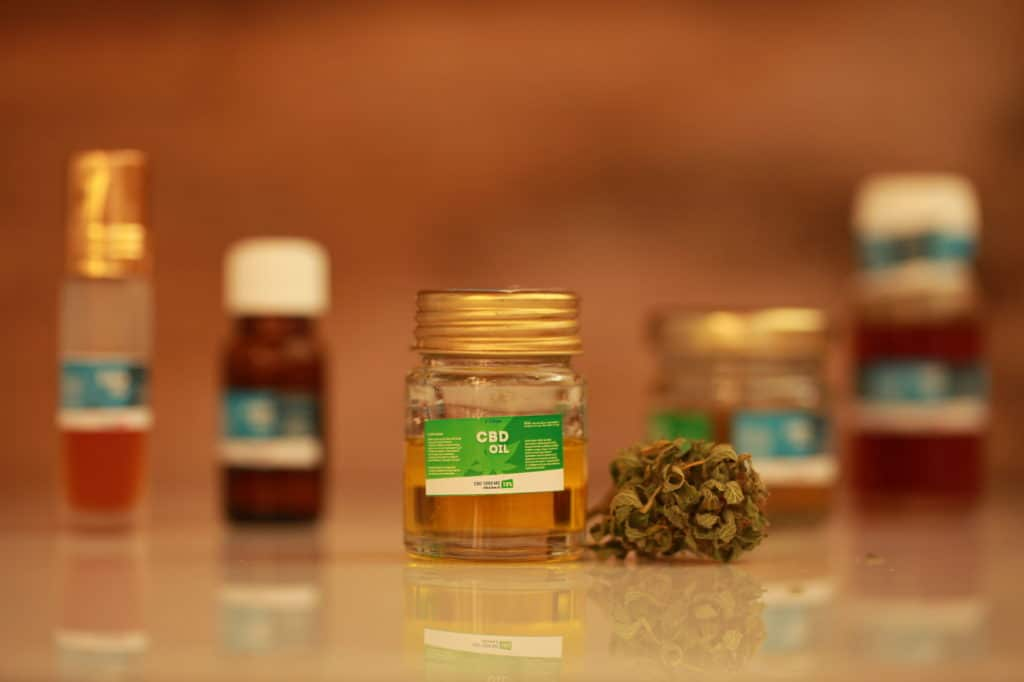 cbd oil bottle with cannabis leaves on its side