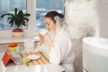 woman drinking tea beside humidifier